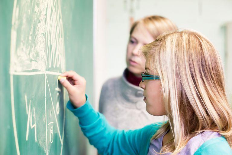 student doing a math problem on a chalkboard