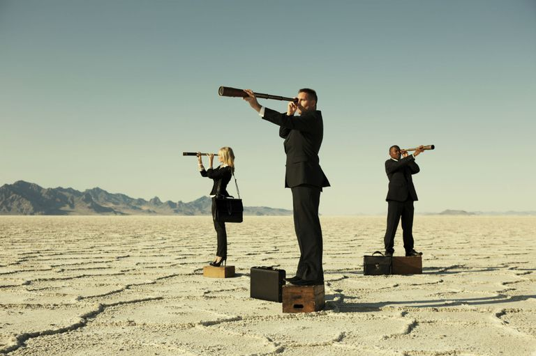 Three business professionals scouting in a desert by looking through telescopes