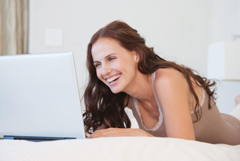 Woman in bed using laptop