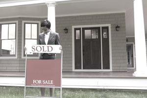 """Real estate agent putting """"SOLD"""" sign on lawn"""