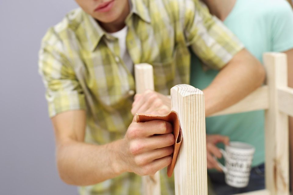 Close-up of a woman watching a young man sandpaper the legs of a wooden chair