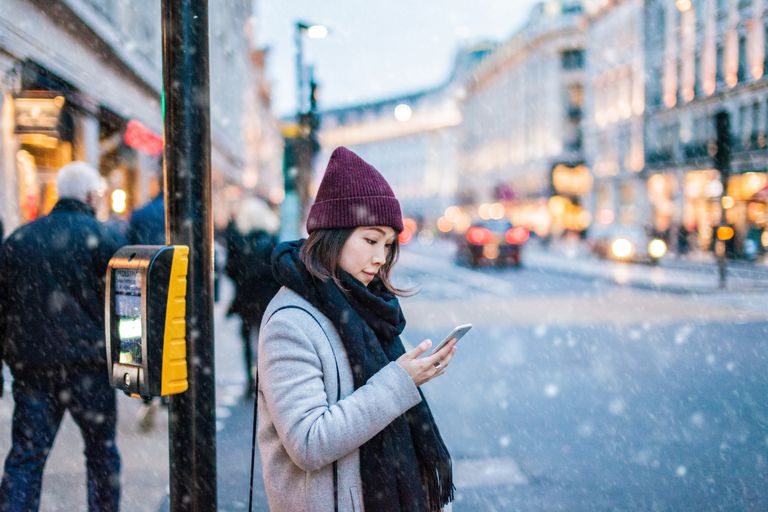 Woman using phone while it's snowing