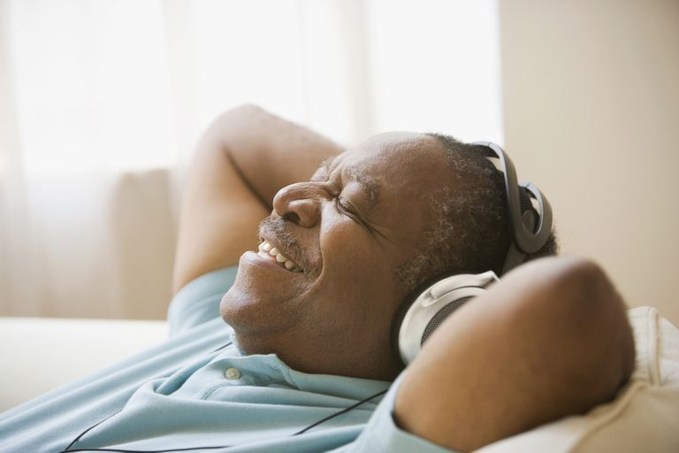 Senior man listening to music with headphones and smiling