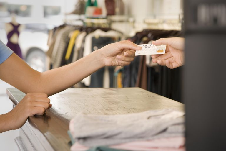 Woman Shopping and Handing Credit Card to Retailer