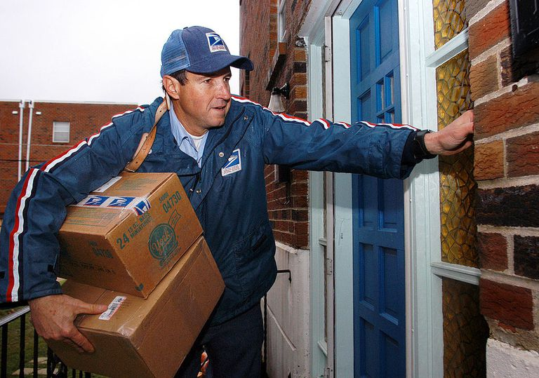 U.S. Postal Service carrier Ron Comly carries parcel packages to a home while delivering mail along his postal route December 17, 2003 in Philadelphia, Pennsylvania. December 17 is expected to be the busiest delivery day for the U.S. Postal Service.
