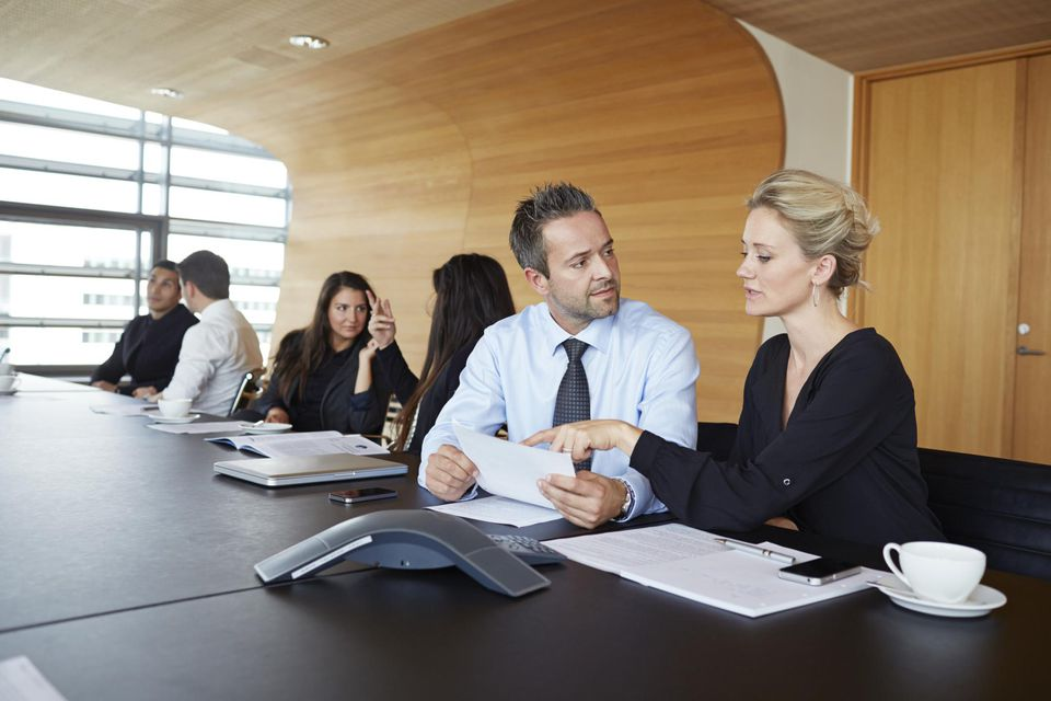 Business people dicussing over papers at meeting