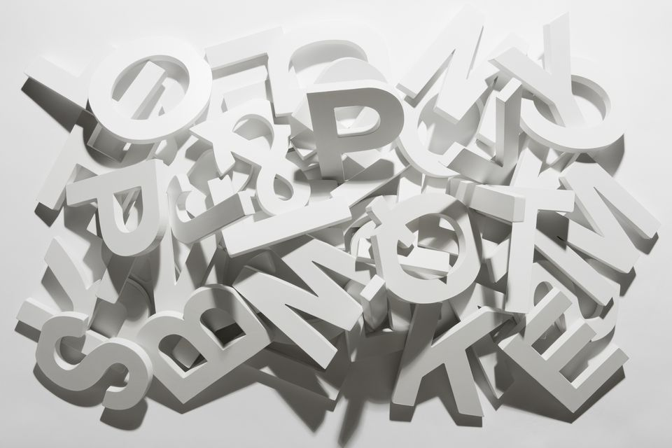 A pile of various white block letters from the alphabet