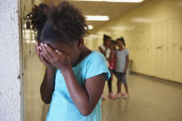 Bullied young girl in school hallway