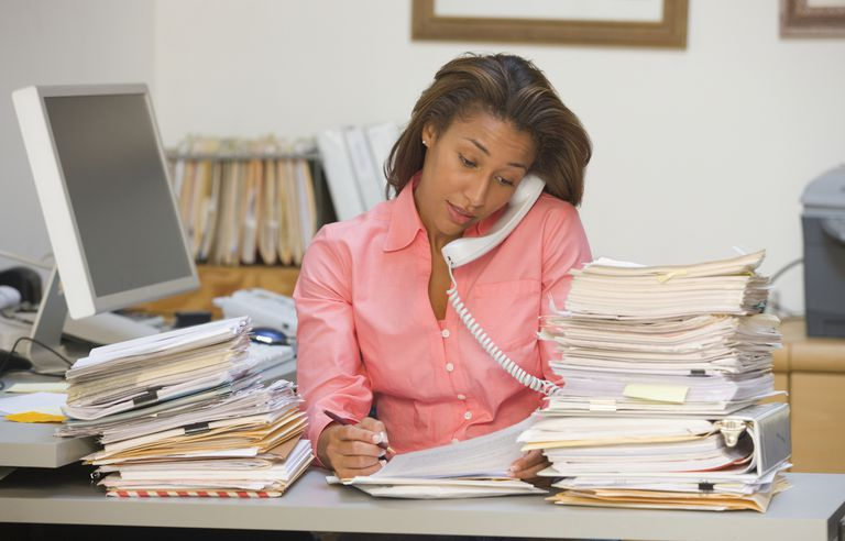 busy office worker on phone with stacks of paperwork on desk