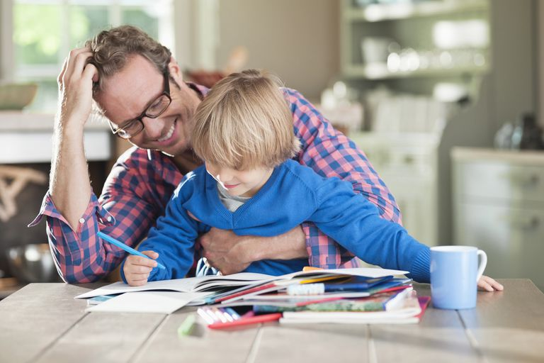 A father helps his son with homework.
