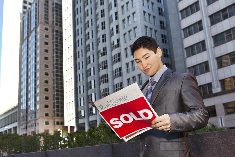 Asian man reading a real estate magazine