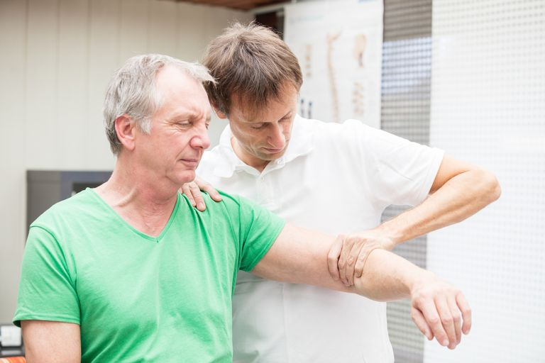 Doctor testing mobility of a patient`s shoulder