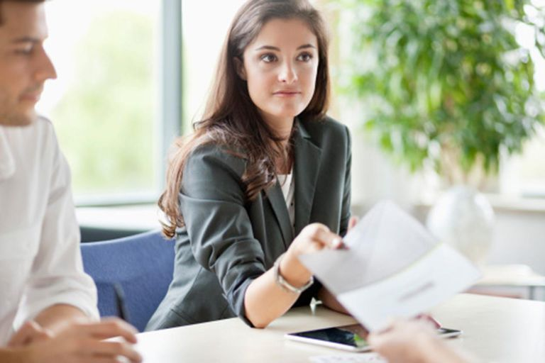woman handing piece of paper over desk in office