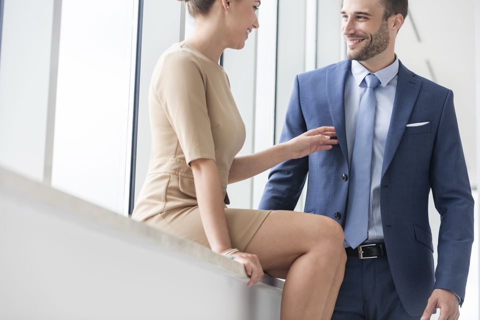 Businessman and woman flirting at office window