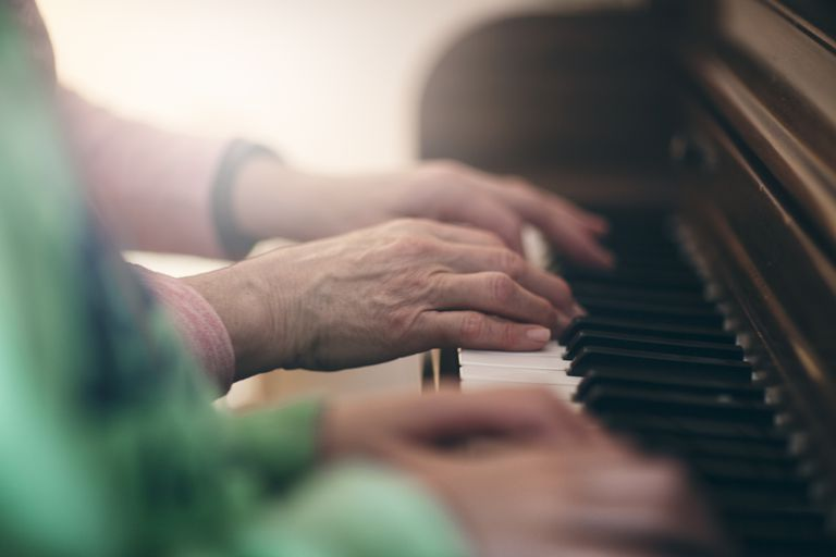 Side view of senior woman and girls hands playing piano together