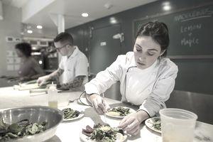 Focused female chef plating salad tweezers restaurant kitchen