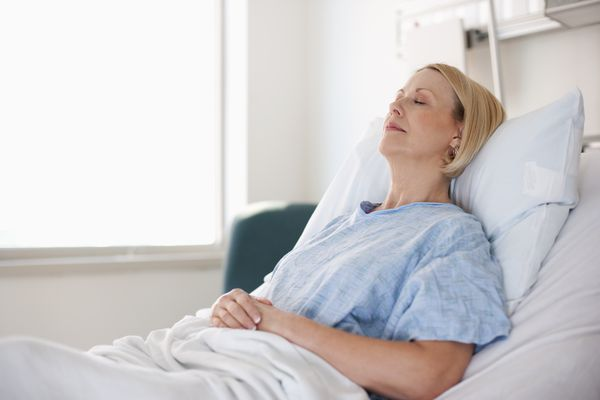 Sleeping Caucasian patient laying in hospital bed