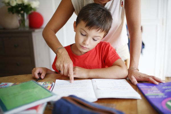 Mom guides boy in doing his homework.
