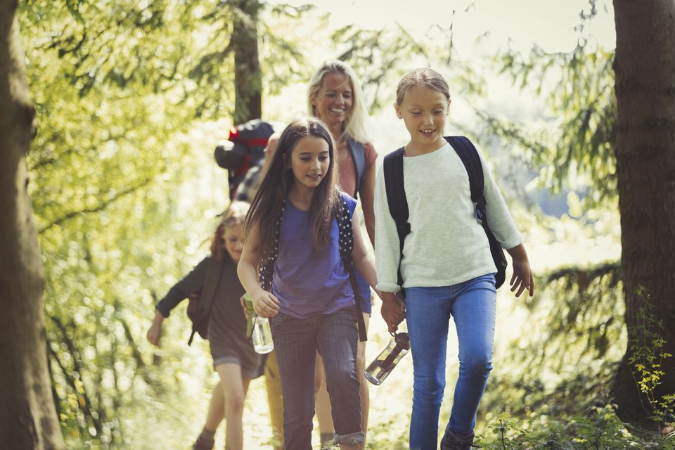 Mother and daughters hiking in woods