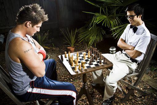 Geek y culturista jugar al ajedrez