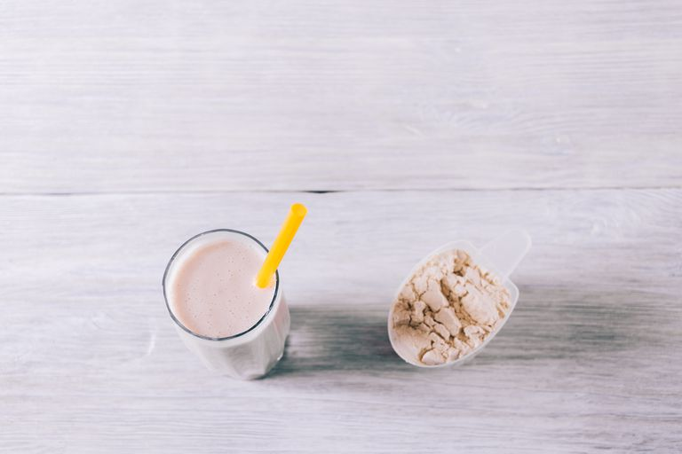 Protein cocktail in a glass and a scoop on a white wooden table