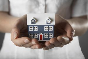 Woman holding model of home, mid section, close-up of hands