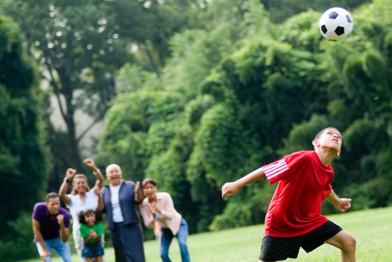 Young boy heading soccer ball as family watches