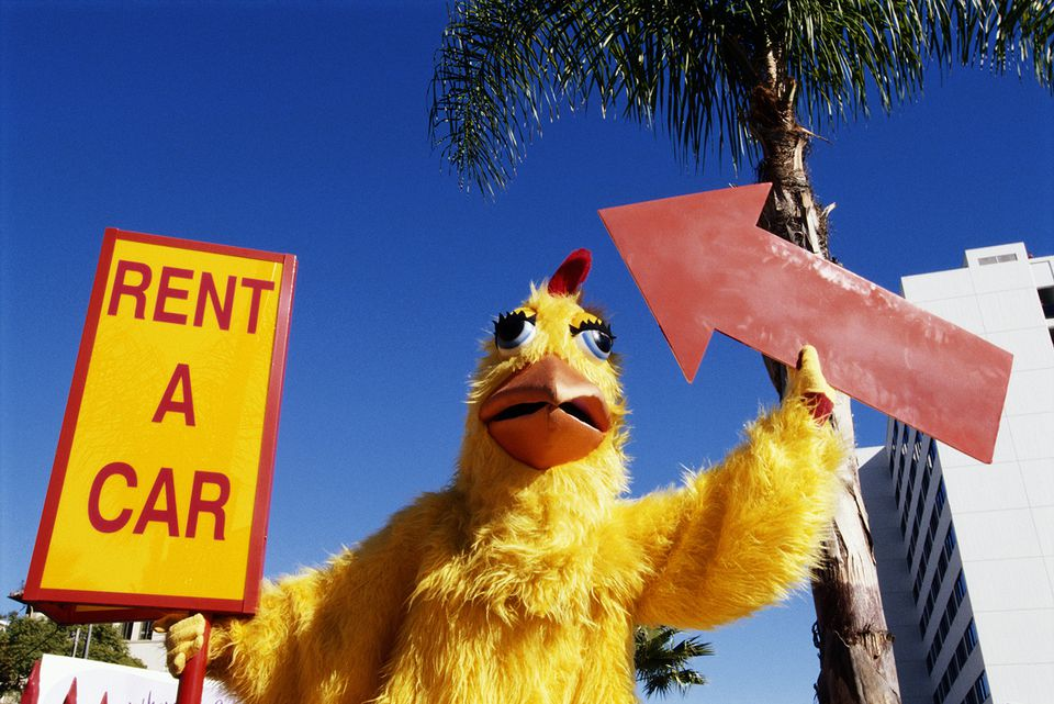 Adult in chicken suit holding arrow sign and 'rent a car' sign on street in California.
