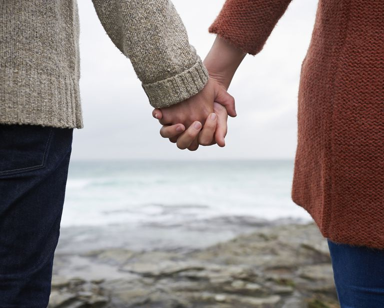Close up of couple holding hands on coastline.