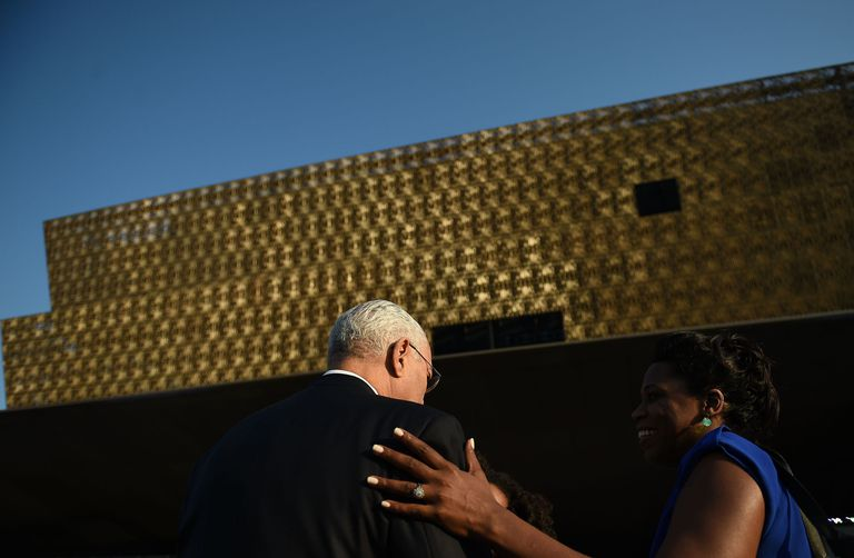 black woman accompanying white-haired black man into a large building