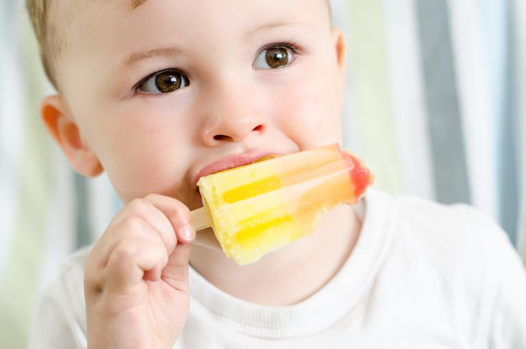 Baby boy eating ice lolly
