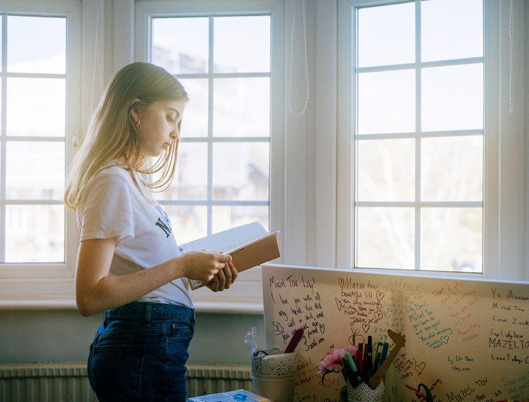 teen girl reading notebook