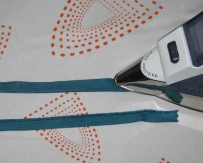 A photo showing how to press the zipper tape flat to sew in an invisible zipper.