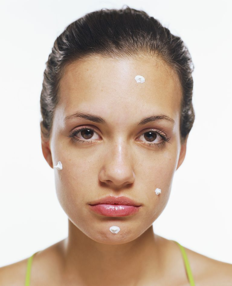 Young woman with dots of cream on face