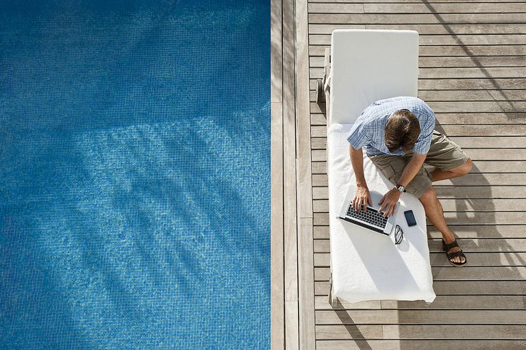 Man on laptop by the pool