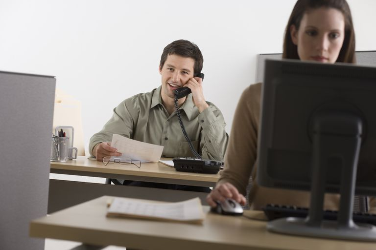 Man using phone in office, woman at computer desktop, (focus on man)