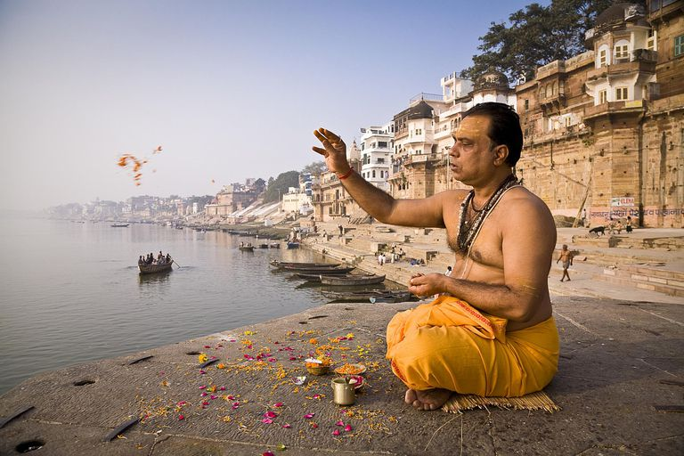 A Brahmin priest prays beside the Ganges River