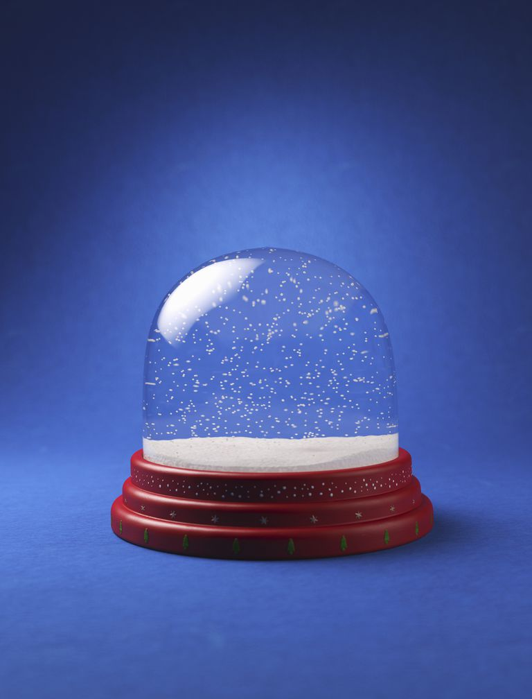 A snow globe in front of a blue background
