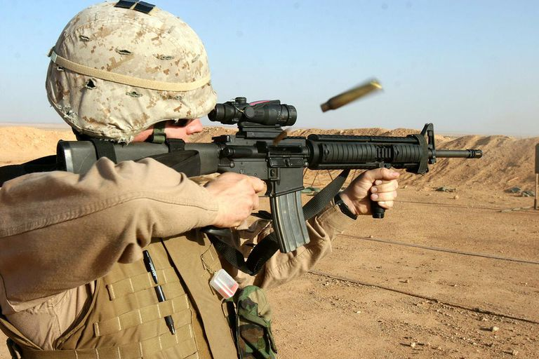 U.S. Marine firing an M16A4 equipped with an ACOG.