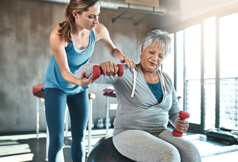 trainer helping senior woman work out with weights
