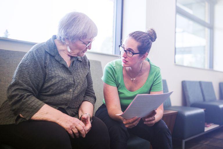 Senior woman having medical paperwork explained