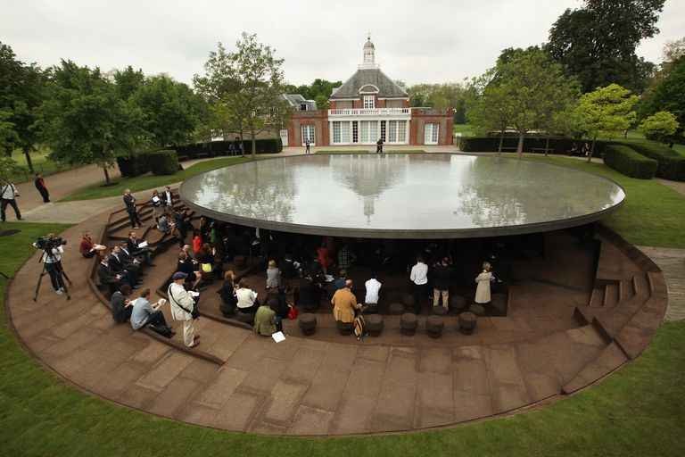 The neoclassical Serpentine Gallery building in the background of what looks like a large wet, flat stone that hovers above underground steps and stools