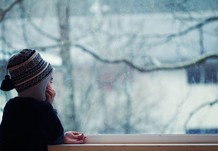 Boy looking out window at winter time