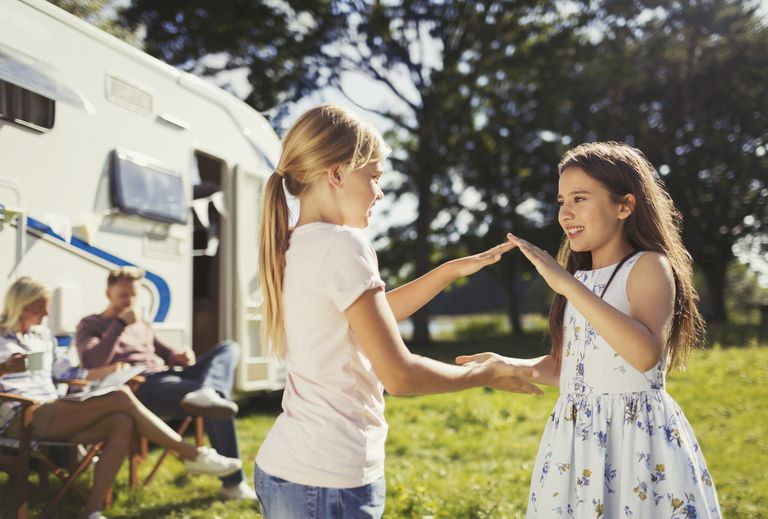 Sisters playing pat-a-cake outside sunny motor home