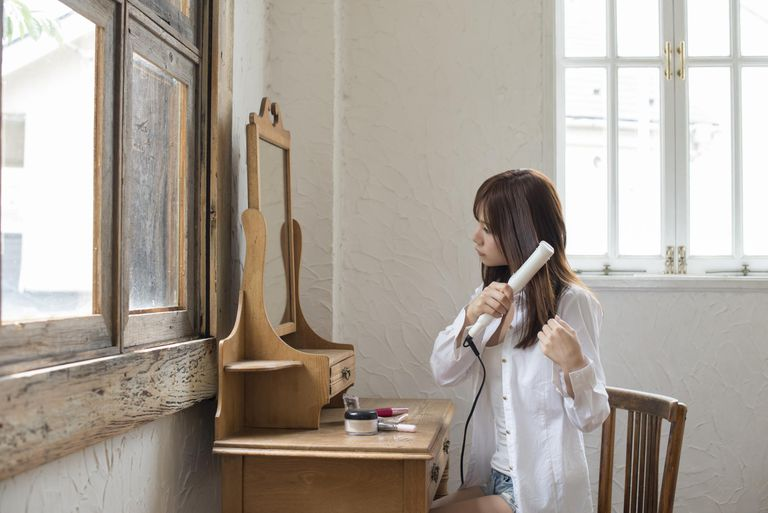 Japanese woman using a hair iron