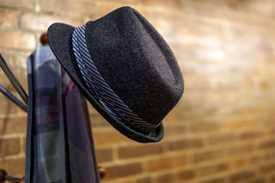 Close-Up Of Hat And Scarf Hanging On Stand By Brick Wall