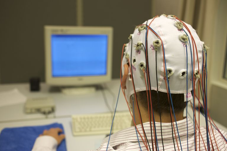man connected with cables for EEG in front of monitor
