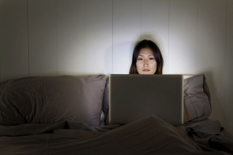 Woman using laptop in bed in a dark room