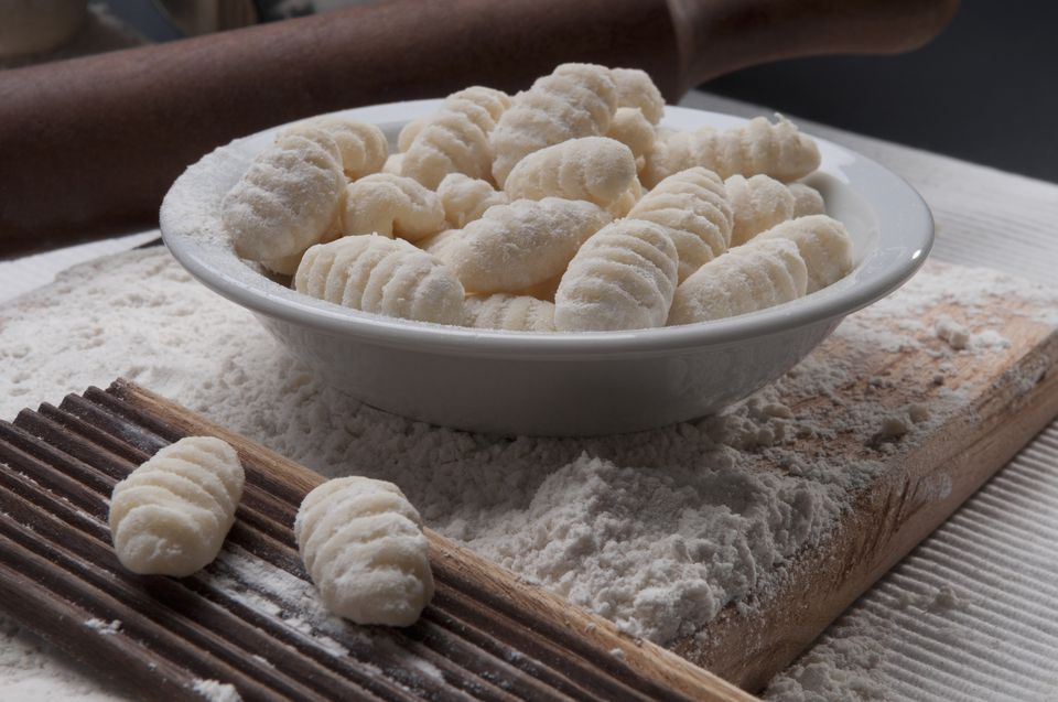 A bowl of homemade gnocchi, next to a wooden gnocchi board