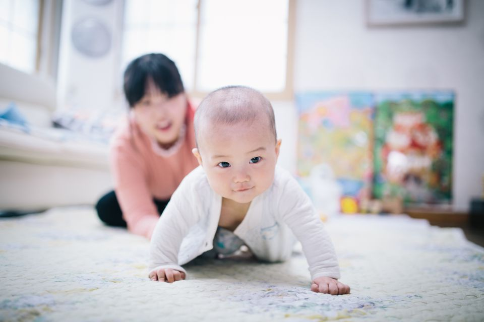mom and baby boy crawling
